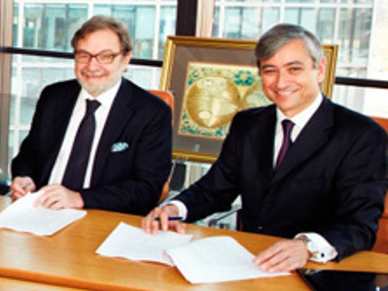 Juan Luis Cebrián, presidente del Grupo PRISA, y Manuel Inocencio Expósito, director financiero de PqHdM, firmando el acuerdo en las oficinas de la revista alternativa digital madrileña de Lavapiés (Madrid)