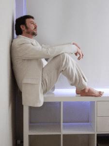 Ángel Petisme descalzo y de blanco meditando sobre una estantería blanca en un fondo blanco virginal